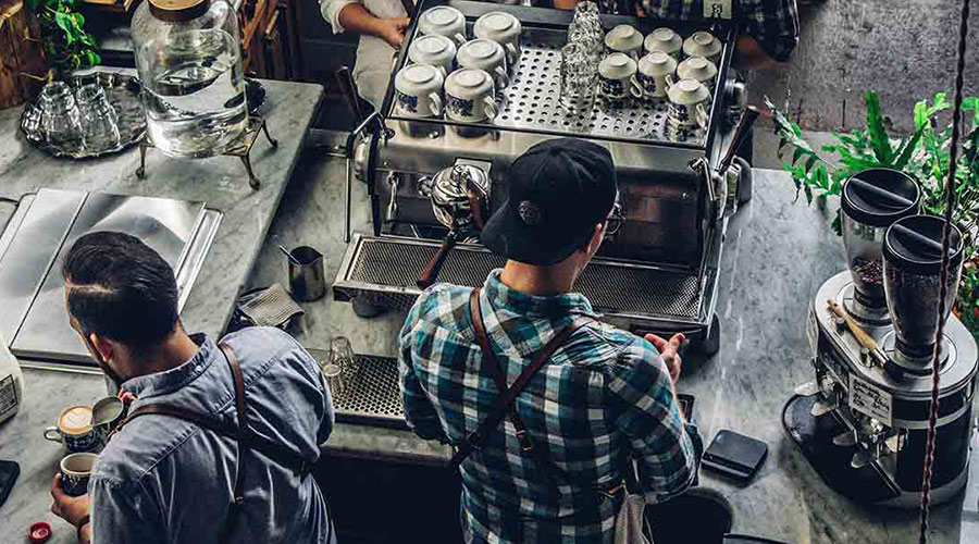 Two men preparing coffee at a coffee shop counter