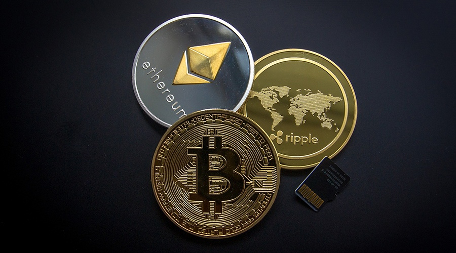 Bitcoin, ethereum and ripple coins stacked next to a SIM card