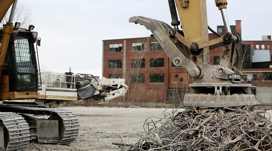 Excavator pressing down on a pile of scrap metal