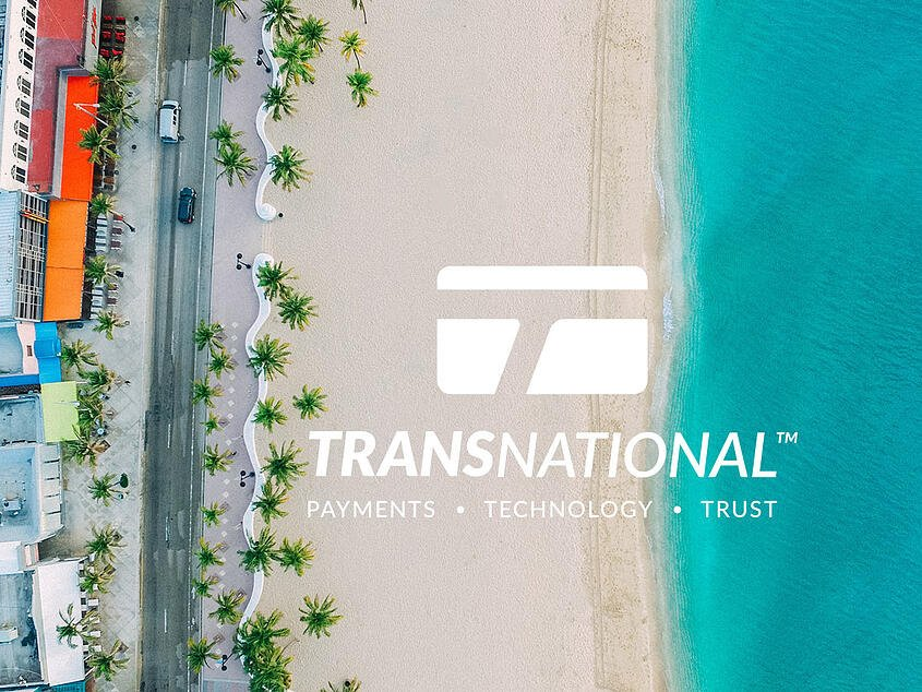 Aerial view of the beach and oceanside road with TransNational Payments logo