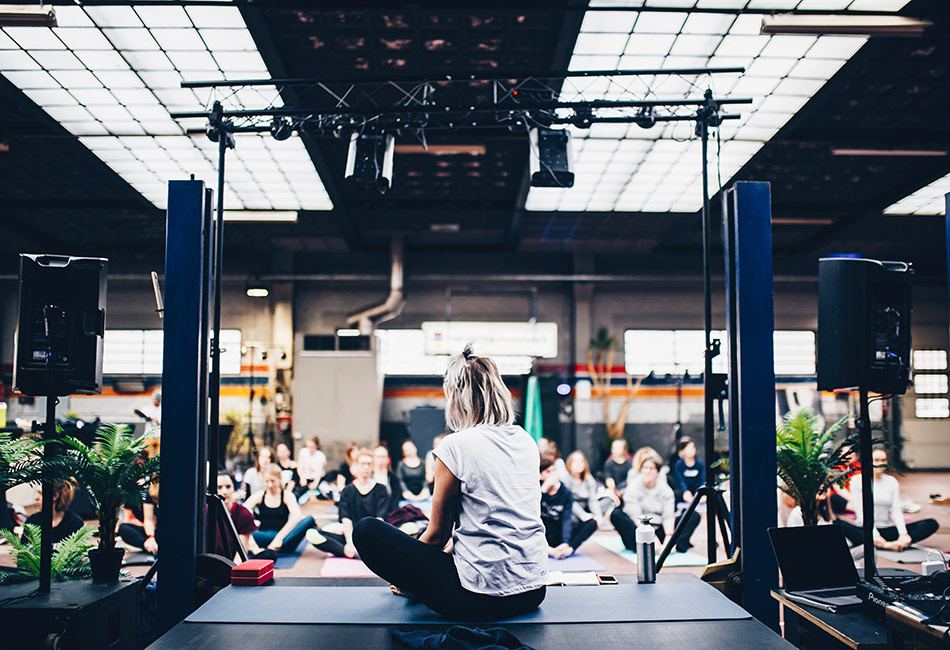 Yoga instructor sitting on stage facing a room full of students
