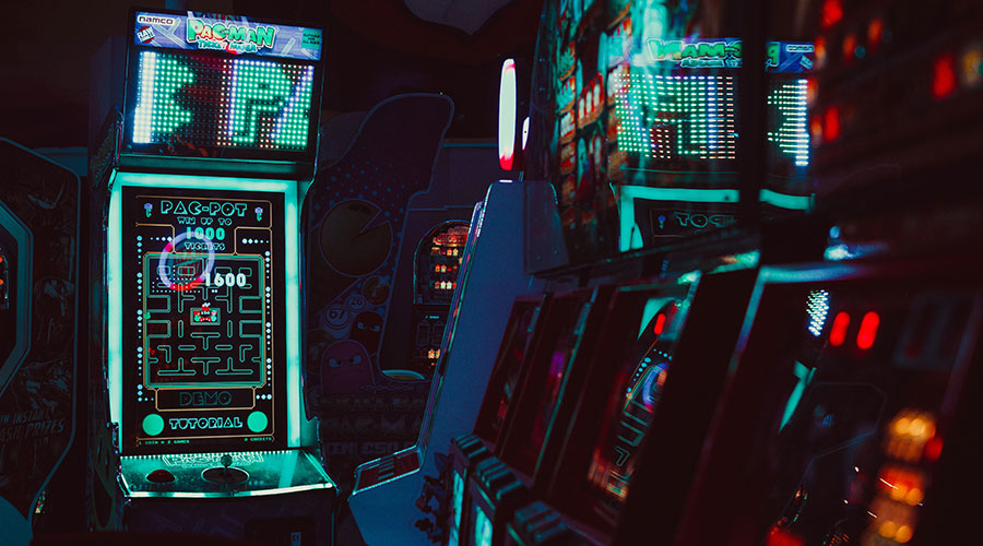 Neon arcade video game machines in a dark room