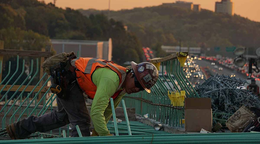 Roofer wearing a safety hat on a roof at sunset