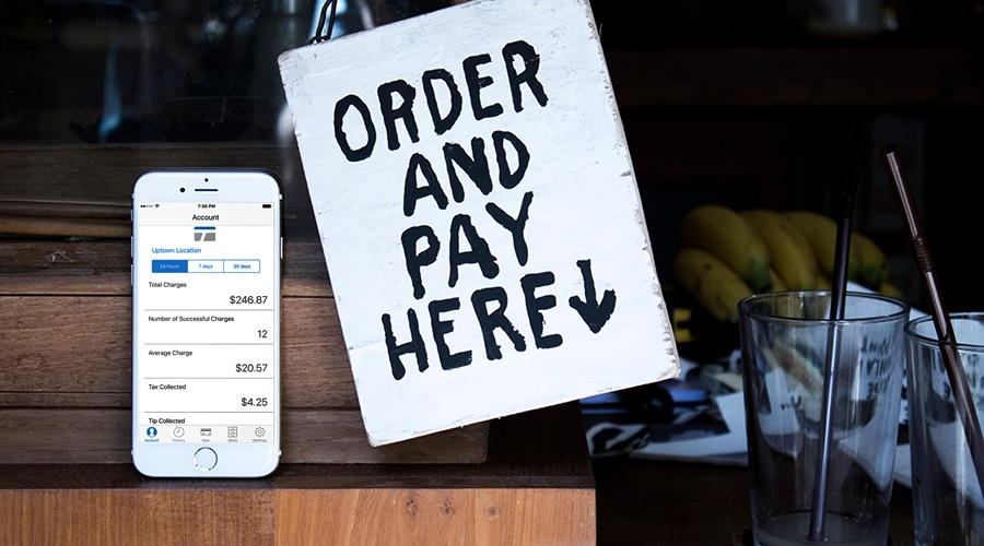 TransNational Payments mobile payment app next to a order and pay here sign at a small business location