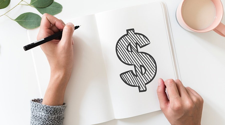 Woman drawing a large dollar sign in a white notebook